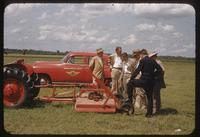 A committee examines a deck mower attached to a tractor at the Memphis Municipal Airport, 1955
