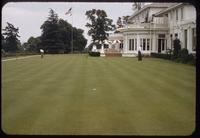 View of the practice green, with 2 golfers, in front of the clubhouse of the Los Angeles Country Club, 1954